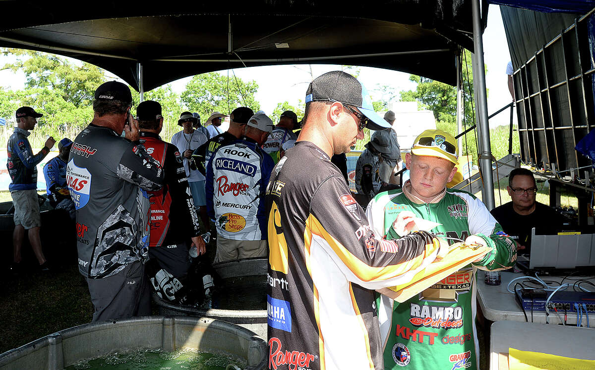Little Cypress - Mauriceville fishing team member Reece Hebert completes post-weigh-in paperwork with anglers after they exit the stage while he and teammates volunteer behind the scenes at the Bassmaster Elite Series tournament in Orange. Photo taken Thursday, June 7, 2018 Kim Brent/The Enterprise