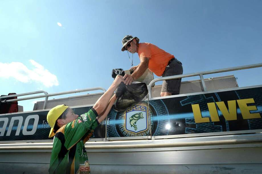 Little Cypress - Mauriceville fishing team member Wyatt Wozniak hands off the next bag of anglers' catch after weigh-in while working at the live release station with contract tournament assistant Mike Macon as he and teammates volunteer behind the scenes at the Bassmaster Elite Series tournament in Orange.
