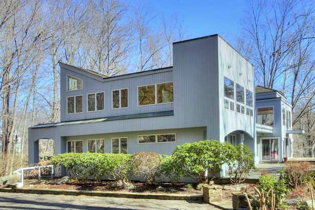 The gray contemporary house at 23 Riverbank Road in the Lower Weston area sits on a 2.2-acre level and sloping property on the banks of the Saugatuck River.