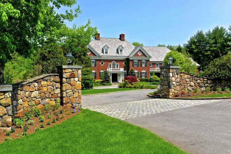 Stone pillars topped with lanterns stand at the entrance to this property at 723 Oenoke Ridge Road on a private cul-de-sac.