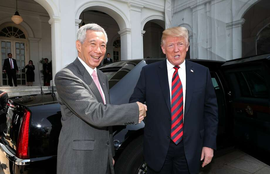 In this photo released by the Ministry of Communications and Information of Singapore, U.S. President Donald Trump, right,  and Singapore Prime Minister Lee Hsien Loong, left, shake hands in Singapore, ahead of a summit with North Korean leader Kim Jong Un, Monday, June 11, 2018. (Ministry of Communications and Information Singapore via AP) Photo: Associated Press