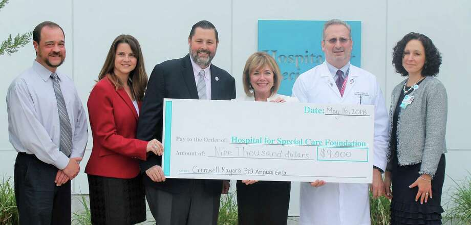 The Cromwell mayor's ball donated $9,000 to the Hospital for Special Care in New Britain recently. The funds will be used to further its research into amyotrophic lateral sclerosis and treatment of patients with the disease. Among those at the check passing ceremony were state Rep. Christie Carpino, second from left, and Mayor Enzo Faienzo, third from left. Photo: Contributed Photo