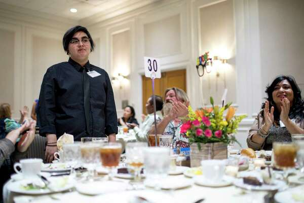 Dakota Koppenol stands to be recognized at a districtwide banquet for valedictorians. He is wearing a new shirt, which his principal, Diana Del Pilar, bought for him earlier in the evening.