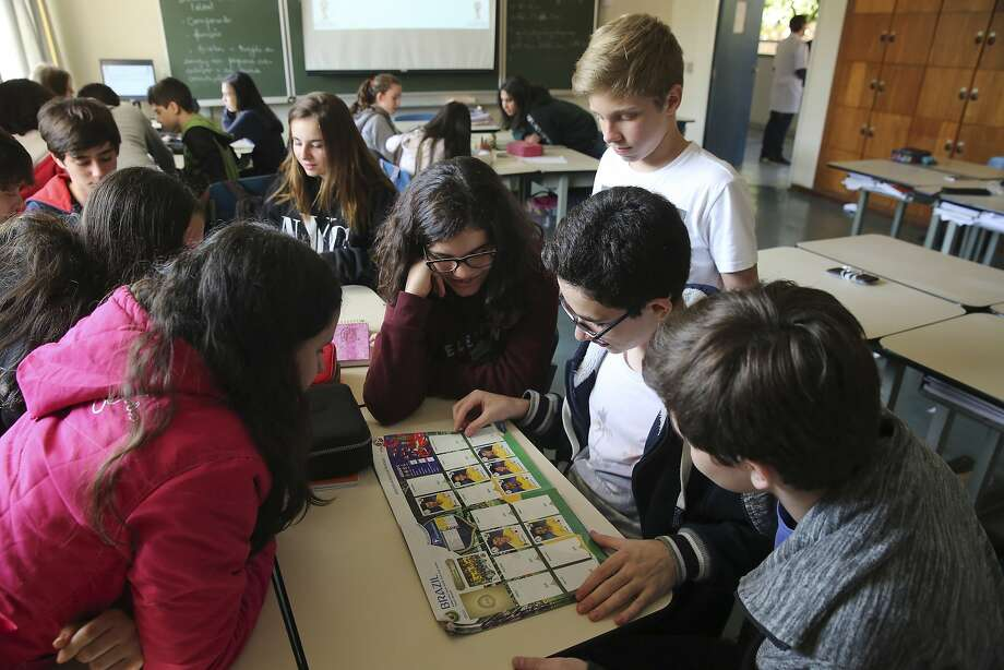 Students look at a World Cup sticker book during their Portuguese class in Sao Paulo, Brazil. The books have been huge sellers in the U.S. as well. Photo: Photos By Andre Penner / Associated Press