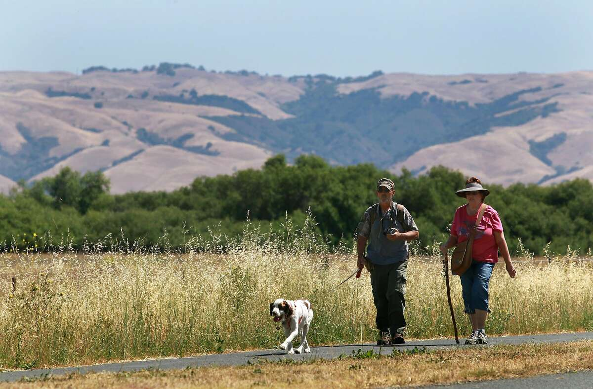 Day hikers walk on a trail through privately-owned land that will soon be a part of Coyote Hills Regional Park in Fremont, Calif. on Tuesday, June 3, 2014. The Patterson family is donating a large parcel of ranch land to the East Bay Regional Parks District, significantly increasing the size of the Coyote Hills open space.