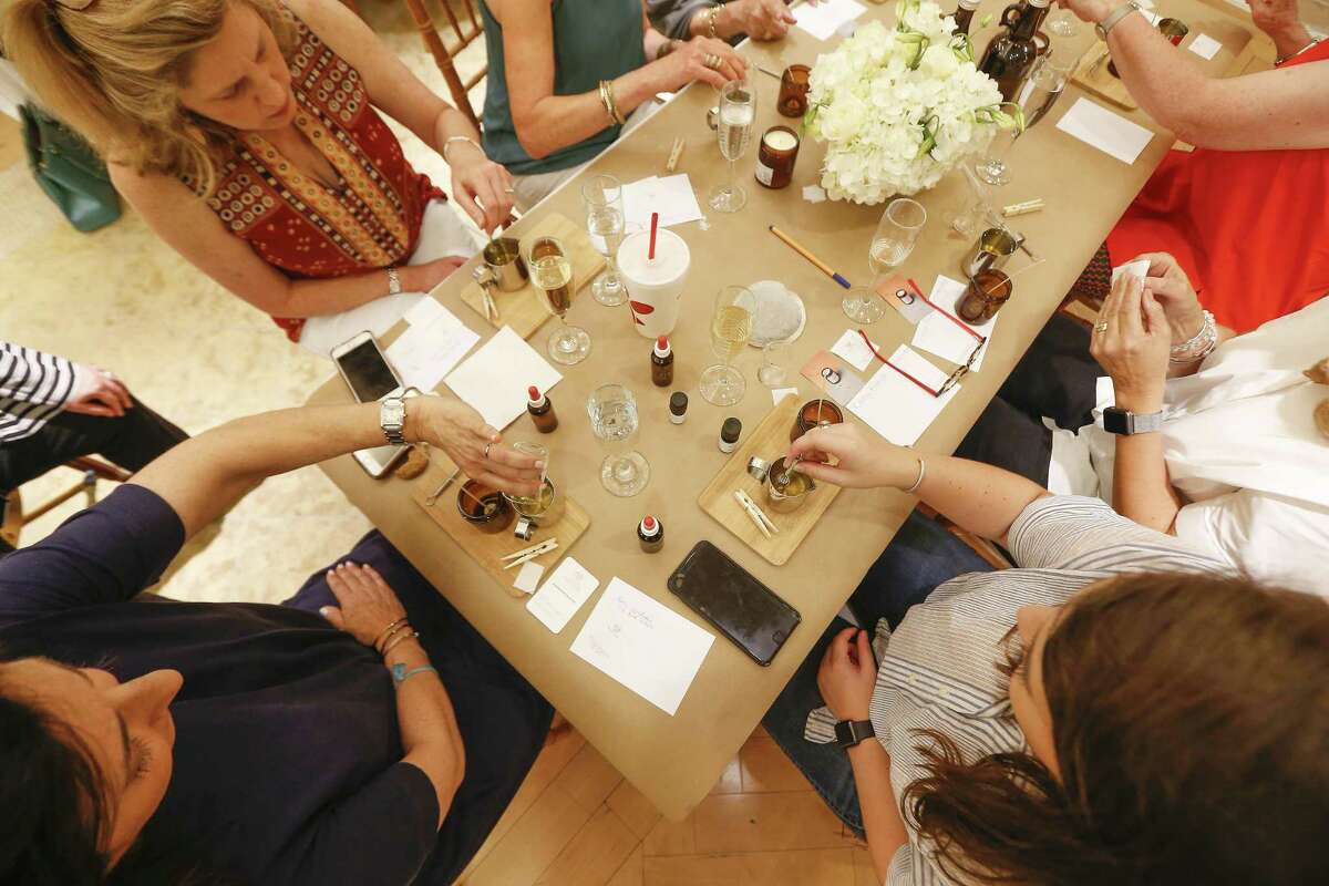 Candle-making workshop participants mix their unique fragrance at Neiman Marcus.