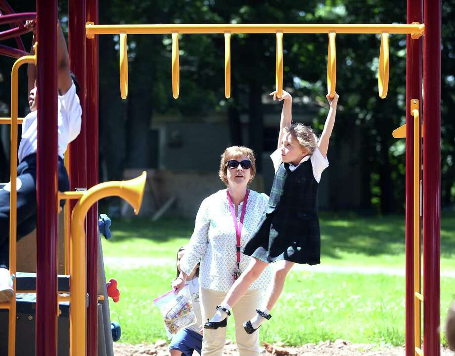 Kindergartner Alexandra Saranich, 6, climbs across the monkey bars under the watch of her teacher, Theresa McKeon, after a ribbon-cutting ceremony for the St. Rita School playground in Hamden Monday. Photo: Arnold Gold / Hearst Connecticut Media / New Haven Register
