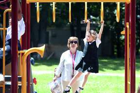 Kindergartner Alexandra Saranich, 6, climbs across the monkey bars under the watch of her teacher, Theresa McKeon, after a ribbon-cutting ceremony for the St. Rita School playground in Hamden Monday.