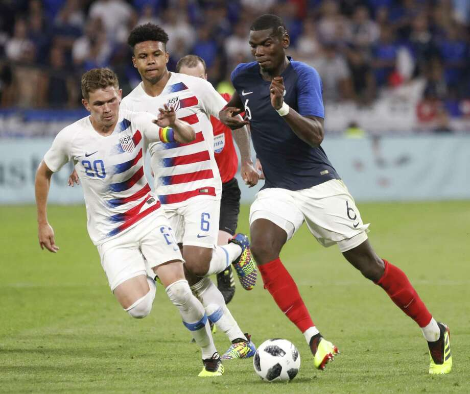 France's Paul Pogba, right, battles for the ball with United States' Will Trapp, left, and Weston Mckennie during a friendly soccer match between France and USA at the Groupama stadium in Decines, near Lyon, central France, Saturday, June 9, 2018. (AP Photo/Laurent Cipriani) Photo: Laurent Cipriani, STR / Associated Press / Copyright 2018 The Associated Press. All rights reserved.