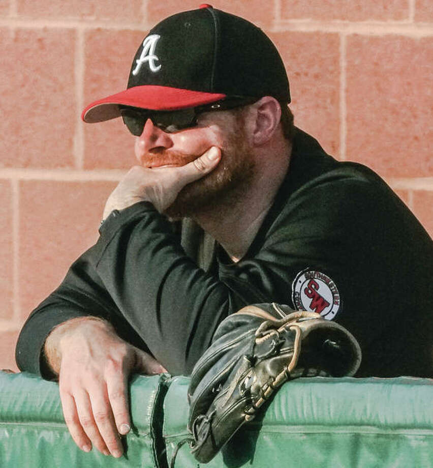 Alton baseball coach Todd Haug watches his team from the dugout during a game last season at Alton High in Godfrey. Haug, succumbing to pressure for the district to remove him as coach, resigned Monday. Photo:       Nathan Woodside / For The Telegraph