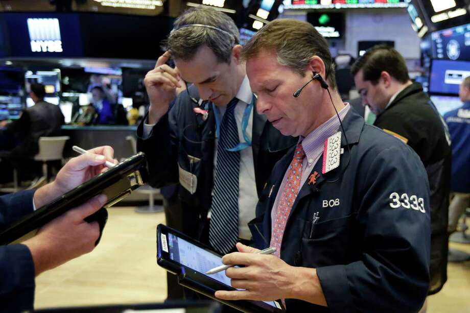 Traders Gregory Rowe, center, and Robert Charmak work on the floor of the New York Stock Exchange, Monday, June 11, 2018. Stocks are opening higher on some corporate deal news. (AP Photo/Richard Drew) Photo: Richard Drew / AP