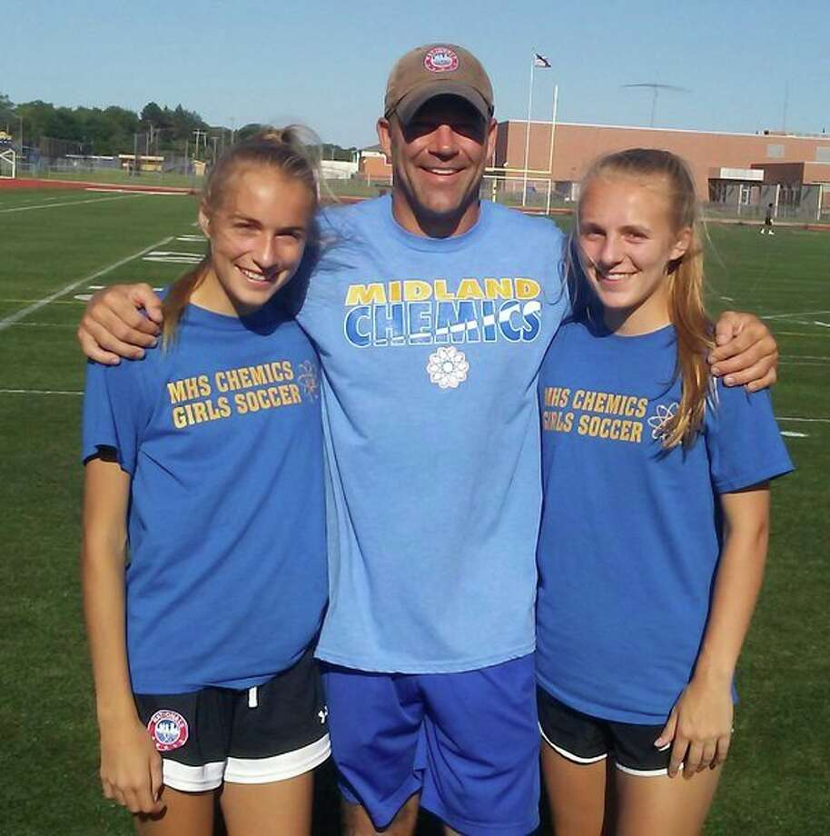 Sisters Chloe Rajewski, left, and Riley Rajewski, right, are shown with their father, Dan Rajewski. The sisters are teammates on the first Midland High girls soccer teamto have reached the state semifinals since 1987. The coach of that team was JoAnn Rajewski, Dan's mother and Chloe and Riley's grandmother. Dan was also the manager of that team.