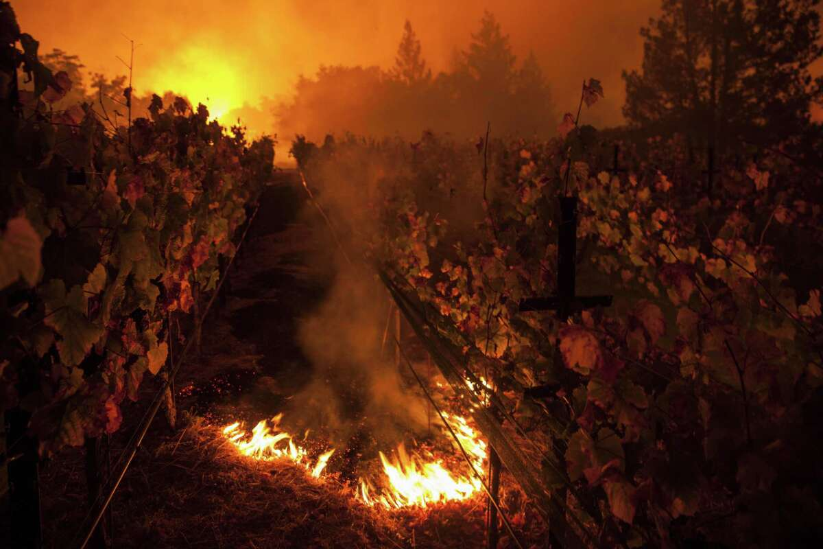 The Nuns Fire burns through Paras Vineyards while the main structure on the property is ablaze in the background west of downtown Napa on Oct. 10, 2017.