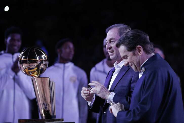 Warriors owners Joe Lacob, center, and Peter Guber, right, after they recieved their championship rings from NBA Commisisoner Adam Silver before the first half as the Golden State Warriors played the Houston Rockets at Oracle Arena in Oakland, Calif., Tuesday, October 17, 2017.