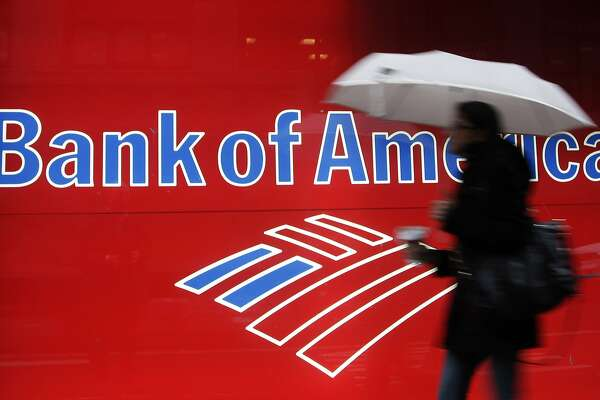 In this Dec. 7, 2012 photo, a woman passes a Bank of America office branch, in New York. Bank of America said Jan. 19, 2012, it made $2 billion in the last three months of 2011 from selling its stake in a Chinese bank and selling debt. That offset losses and higher legal expenses in its mortgage business. (AP Photo/Mark Lennihan)