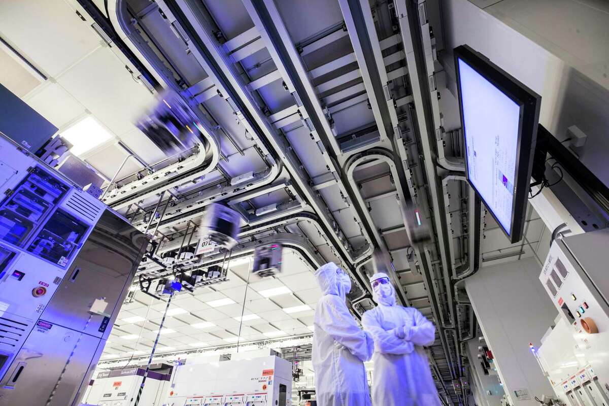 Workers at GlobalFoundries' computer chip factory in Malta. Above them are the motorized tracts that carry the containers known as