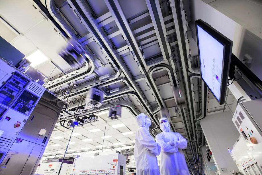 "Workers at GlobalFoundries' computer chip factory in Malta. Above them are the motorized tracts that carry the containers known as ""foups"" in which silicon wafers are transported. Photo: Provided By GlobalFoundries"
