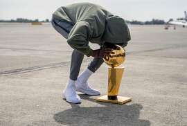 Golden State Warriors' Kevin Durant kisses the NBA Championship trophy as he arrives from Cleveland, Ohio at Landmark Aviation in Oakland, Calif. Saturday, June 9, 2018. after defeating the Cleveland Cavaliers in the NBA Finals.