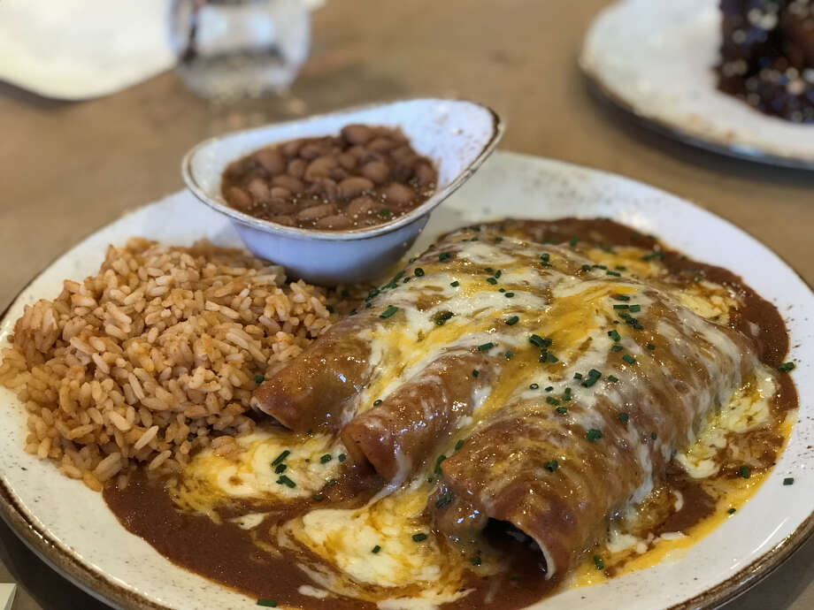 Chef Ronnie Killen is offering Tex-Mex dishes on his dinner menu at Killen's Barbecue in Pearland. He hopes to one day open a Tex-Mex restaurant in Houston, he said. Shown: brisket enchiladas with rice and charro beans.