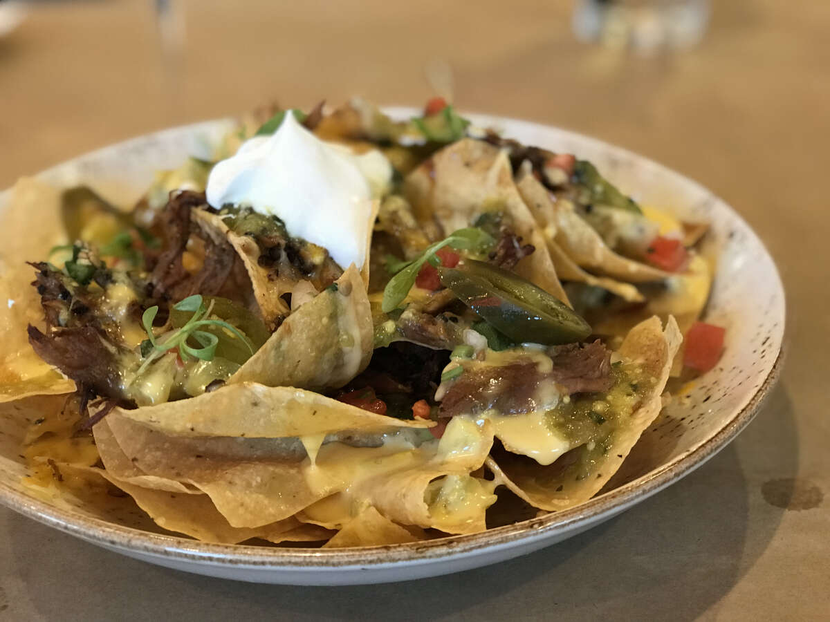 Chef Ronnie Killen is offering Tex-Mex dishes on his dinner menu at Killen's Barbecue in Pearland. He hopes to one day open a Tex-Mex restaurant in Houston, he said. Shown: pulled pork nachos with melted cheese and pico de gallo.