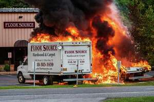 Halfmoon Fire Department firefighters at the scene of a fire on Sunday, June 10, 2018, that State Police said was caused by a drunken driver.His SUV allegedly became airborne and crashed into the back of two box trucks in the parking lot of Floor Source on Route 9. (Sean Organ)