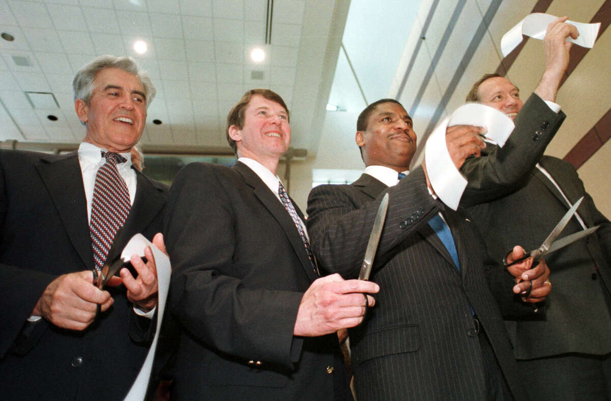 Times Union photo by CINDY SCHULTZ -- MONDAY, JUNE 1, 1998 -- COLONIE -- Gov. George Pataki, right, holds up a piece of the ribbon after the ribbon cutting ceremony Monday at the Albany International Airport. Also participating in the festivities are, from left, Sen. Joseph Bruno, Rep. Michael McNulty and U.S. Secretary of Transportation Rodney Slater.