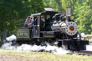 A group of train fans get a ride on the 1925 Baldwin Locomotive at the Antique Machinery Fall Festival in Kent.