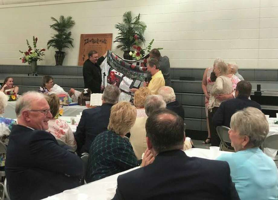 Retiring Pastor Timothy Loehrke of Cross Lutheran Church accepted a number of gifts, including this memory quilt, from various congregation members and church groups at a retirement luncheon Sunday in Pigeon.