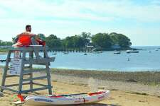 Lifeguard Connor Maul keeps an eye on things at Weed Beach, Sunday, Aug. 13, 2017, in Darien, Conn.