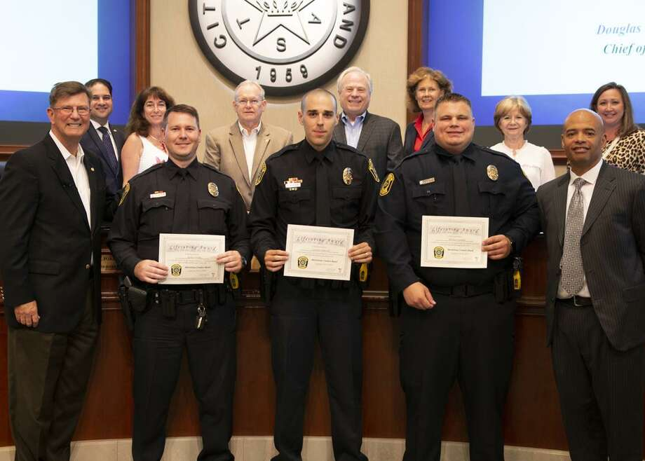 Sugar Land Mayor Joe Zimmerman and the Sugar Land City Council recently honored three Sugar Land Police officers with Life Saving Awards for their efforts rescuing a woman from near-drowning after she fell asleep at the wheel and accidentally drove her car into deep water. Pictured from left are Mayor Joe Zimmerman, Officers Robert Wilks, Garrett Driscoll, Michael Candler and Chief Douglas Brinkley. Photo: Courtesy Photo