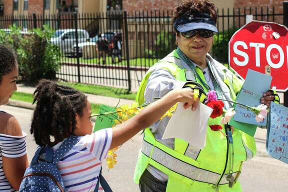 "A student gives Teresa ""Tere"" Regalado Brodowski a flower on the longtime crossing guard's last day on duty near Pomeroy Elementary School."
