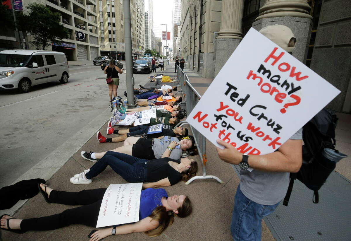 People participate in the March For Our Lives Houston die-in protest on the sidewalk outside the office of United States Senator Ted Cruz, 808 Travis St., Tuesday, June 12, 2018, in Houston. The protest marks the second anniversary of the Pulse nightclub shooting. Protesters laid down for 12 minutes to honor the lives lost to gun violence and to bring awareness to the need for change in our nation's gun laws.