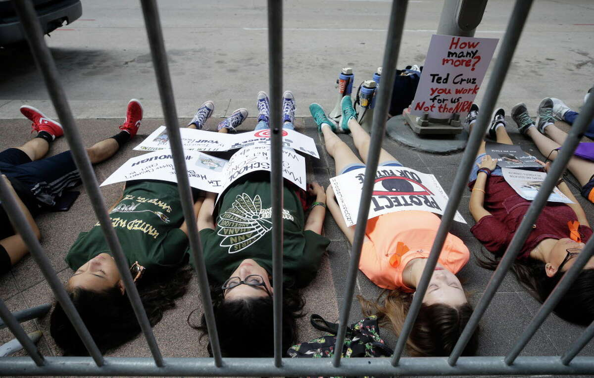 London Delgado, 13, left, her mother, Christina Delgado, along with Sara Reul, 15, Diona Evers, 16, right, and others participate in the March For Our Lives Houston die-in protest on the sidewalk outside the office of United States Senator Ted Cruz, 808 Travis St., Tuesday, June 12, 2018, in Houston. The protest marks the second anniversary of the Pulse nightclub shooting. Protesters laid down for 12 minutes to honor the lives lost to gun violence and to bring awareness to the need for change in our nation's gun laws.