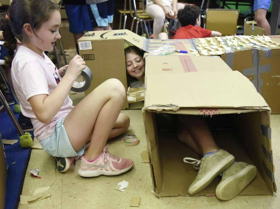 Fourth graders Alexandra Marder, left, and Claire Fugelsang work on their cardboard creation at the Global Cardboard Challenge at Riverside School in the Riverside section of Greenwich, Conn. Monday, June 11, 2018. Now in its second year at Riverside School, students designed and built arcade games and other fun recycled cardboard creations, utilizing STEM components and creativity for the construction process. After completing their own group projects, students got the chance to tour classrooms and play with other students' creations. Photo: Tyler Sizemore / Hearst Connecticut Media / Greenwich Time