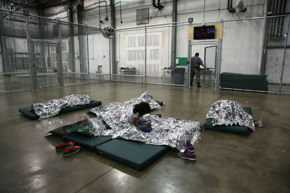 A girl from Central America rests on thermal blankets at a detention facility run by the U.S. Border Patrol on September 8,2014in McAllen, Texas.