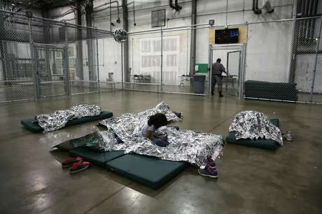 A girl from Central America rests on thermal blankets at a detention facility run by the U.S. Border Patrol on September 8, 2014 in McAllen, Texas. Photo: John Moore/Getty Images