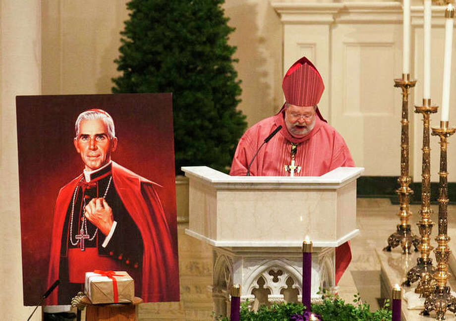 In this Dec. 11, 2011 file photo, Peoria Bishop Daniel Jenky, center, gives a sermon next to a painting of Archbishop Fulton John Sheen and the sealed box of documentation for the alleged miracle performed by Sheen, during a Mass at Cathedral of St. Mary of the Immaculate Conception in Peoria, Ill. The remains of Sheen, who died in 1979 and are at St. Patrick's Cathedral in Manhattan, can be moved to Illinois from New York, nearly 40 years after his death, a New York judge said Friday, June 8, 2018. Joan Sheen Cunningham, 90, believes moving her uncle's remains to Peoria, will improve his cause for sainthood.