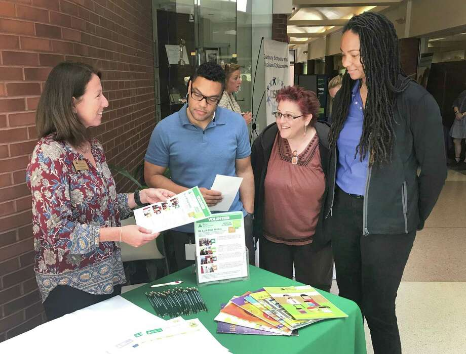 Meg Melagrano of Junior Achievement talks about her organization to Union Savings Bank employees Antony Velez, Tracy Gradia and Synnamon Smith during the bank's inaugural Community Fair held Tuesday, June 13, 2018, at the Galleria in downtown Danbury, Conn. Photo: Chris Bosak / Hearst Connecticut Media / The News-Times