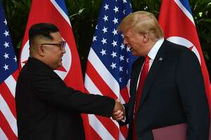 TOPSHOT - North Korea's leader Kim Jong Un (L) shakes hands with US President Donald Trump (R) after taking part in a signing ceremony at the end of their historic US-North Korea summit, at the Capella Hotel on Sentosa island in Singapore on June 12, 2018. Donald Trump and Kim Jong Un became on June 12 the first sitting US and North Korean leaders to meet, shake hands and negotiate to end a decades-old nuclear stand-off. / AFP PHOTO / POOL / Anthony WALLACEANTHONY WALLACE/AFP/Getty Images