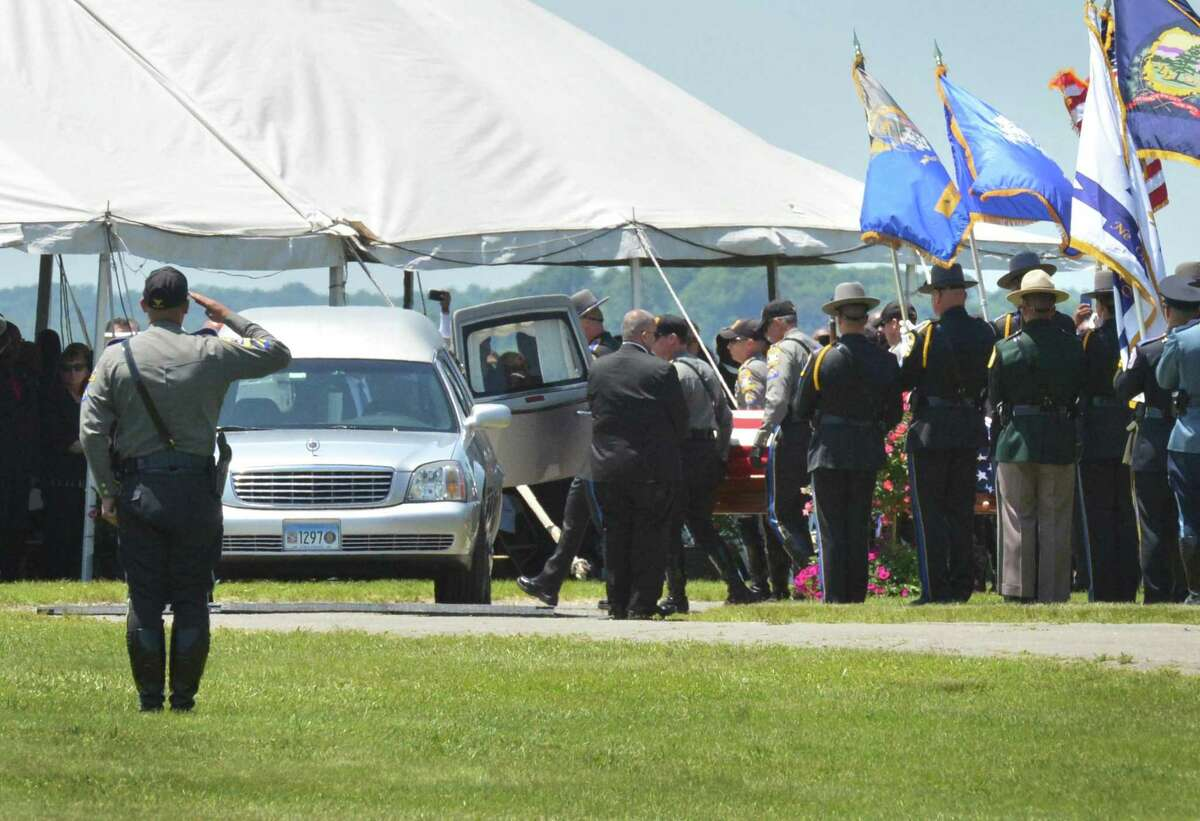 The casket containing Connecticut State Trooper 1st Class Walter Greene Jr. is moved into a hearse during a funeral service at Sherwood Island State Park Tuesday on in Westport.