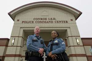 Conroe ISD Police Officer Fred Whiteside, left, and Corporal Brandy Walker pose for a portrait outside the district's police command center in 2017.