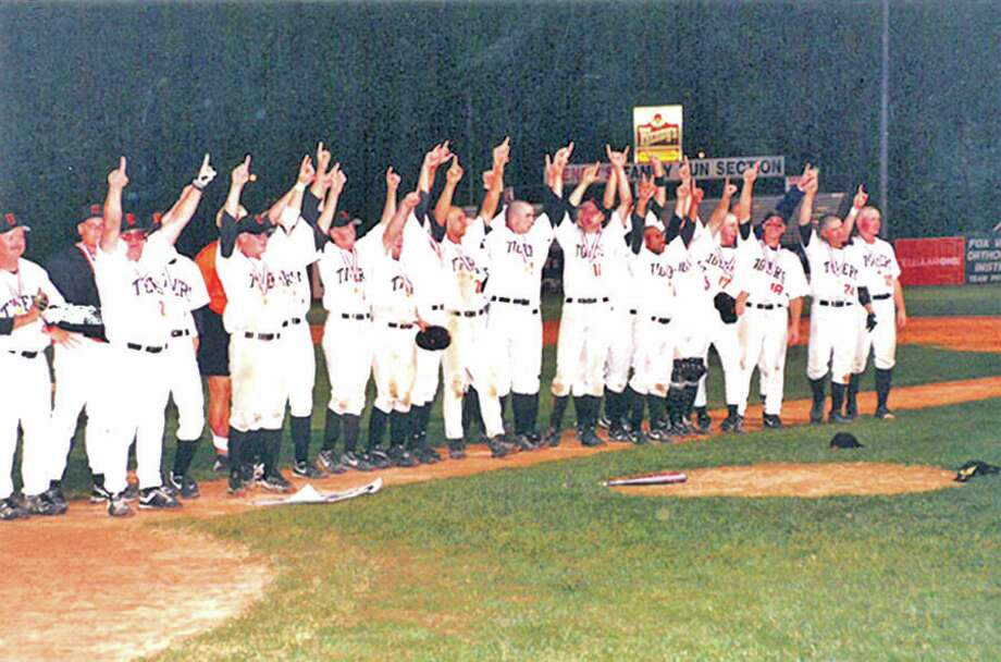 Members of the 1998 Edwardsville baseball team salute the crowd after winning the Class AA state championship.