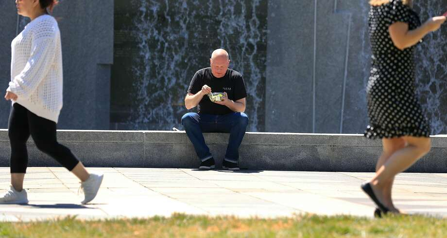 Jon Blunck of San Francisco eats at the Martin Luther King Jr. Memorial and Waterfall at Yerba Buena Gardens, where he  enjoys the sounds and cooling effect. Photo: Lea Suzuki / The Chronicle