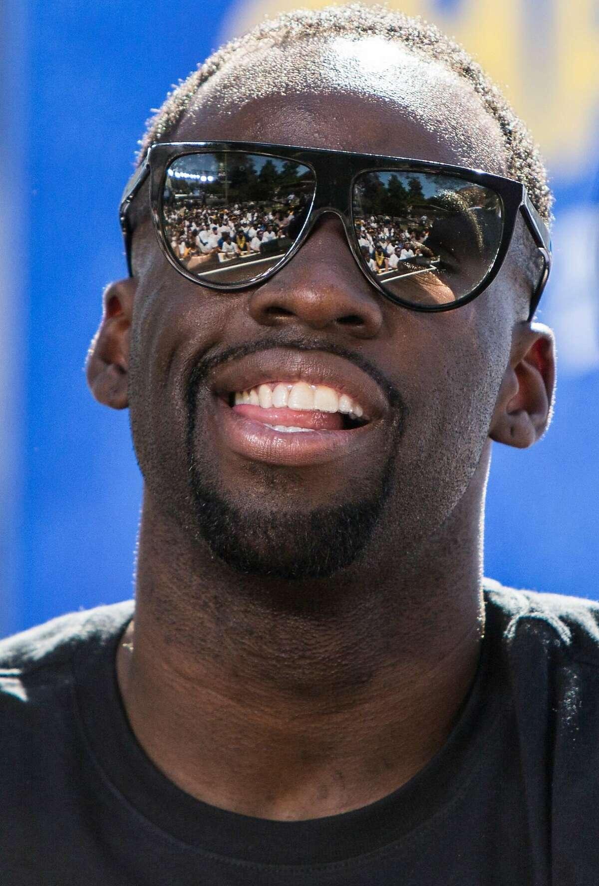 Warriors' Draymond Green flashes his pearly whites at the crowd during an NBC Bay Area Sports question and answer session with the team and coaches before the start of the Golden State Warriors NBA Finals victory parade in downtown Oakland, Calif. Tuesday, June 12, 2018.