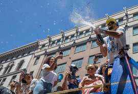 Warriors' Stephen Curry showers the crowd with champagne as he rides by on a bus during the Golden State Warriors NBA Finals Championship parade in downtown Oakland, Calif. Tuesday, June 12, 2018.