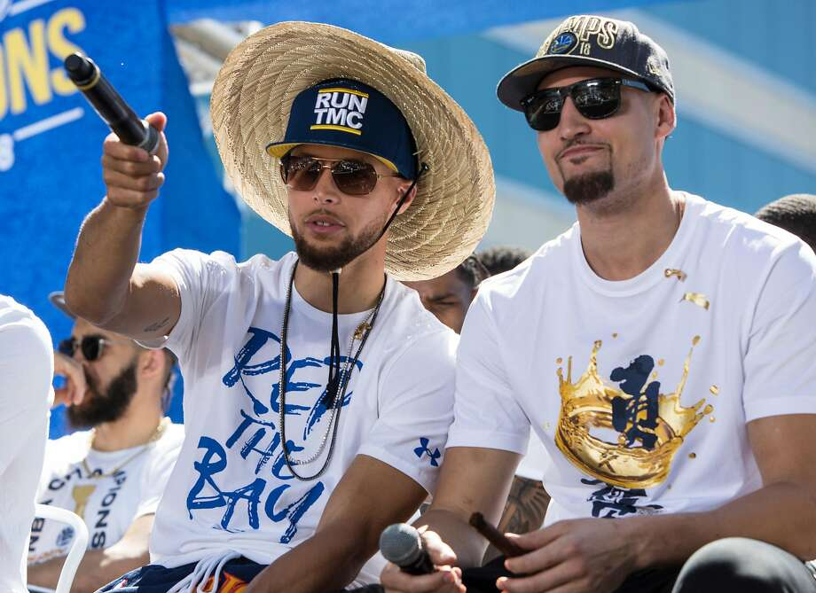 Warriors' Stephen Curry chats with teammate Klay Thompson during an NBC Bay Area Sports question and answer session with the team and coaches before the start of the Golden State Warriors NBA Finals victory parade in downtown Oakland, Calif. Tuesday, June 12, 2018. Photo: Jessica Christian, The Chronicle
