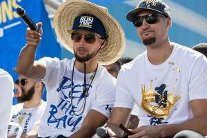 Warriors' Stephen Curry chats with teammate Klay Thompson during an NBC Bay Area Sports question and answer session with the team and coaches before the start of the Golden State Warriors NBA Finals victory parade in downtown Oakland, Calif. Tuesday, June 12, 2018.