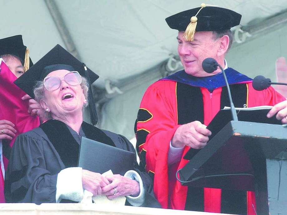 Wesleyan University President Douglas Bennet, right, looks on as Doreen Freeman receives her honorary doctor of humane letters degree during the school's May 2003 commencement in Middletown. Photo: File Photo