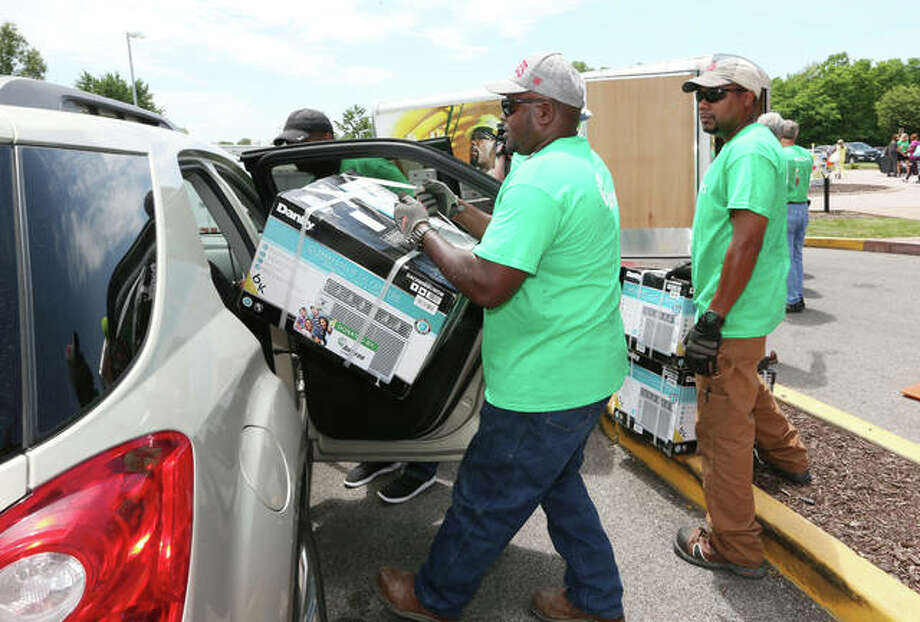 An Ameren Illinois employee-volunteer loads an air conditioning unit into a client's vehicle. Photo:       For The Telegraph