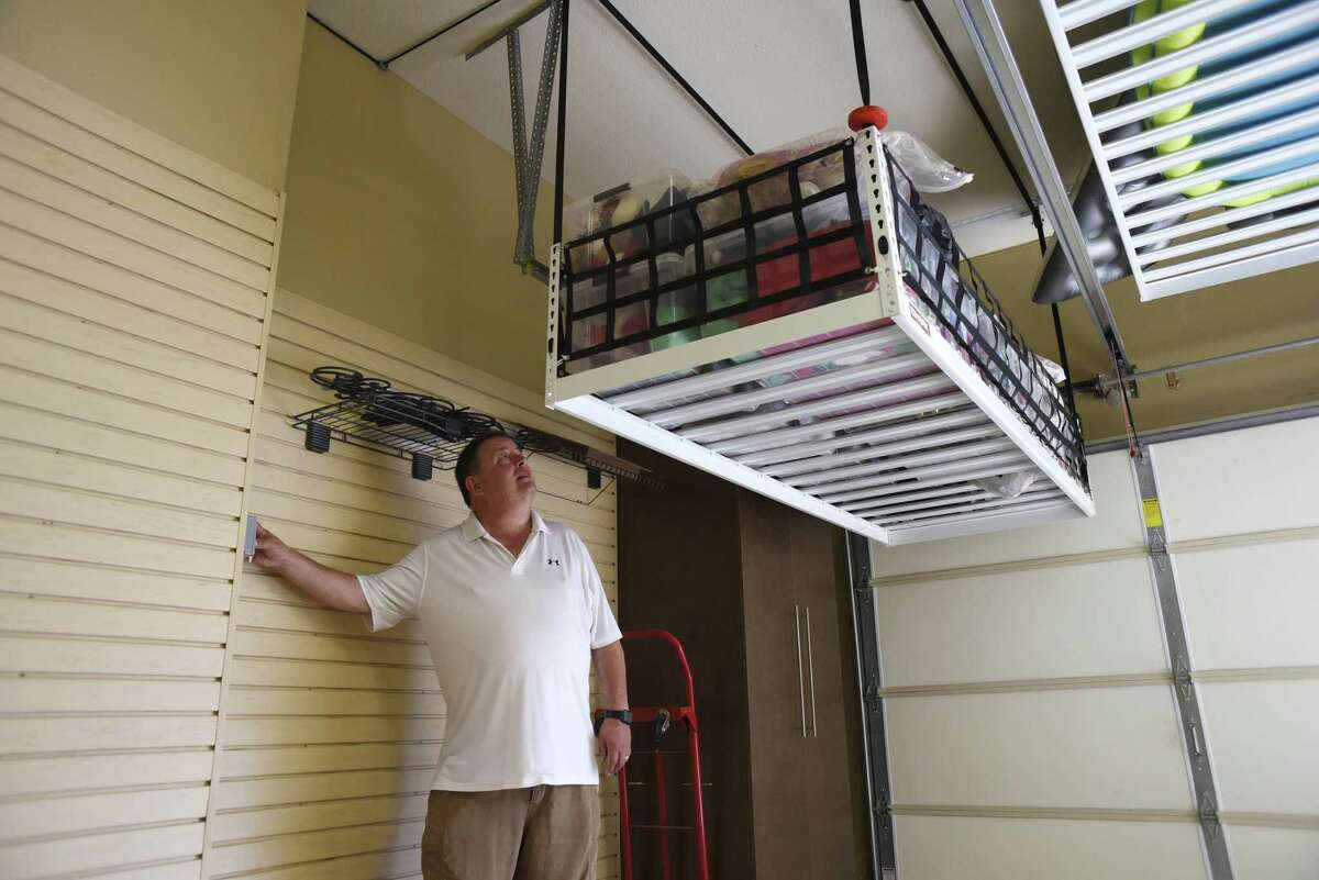 The motorized lift Dennis and Melba Solheim had installed in their garage to store stuff measures 4 feet by 8 feet and rises up and out of the way at the touch of a button.